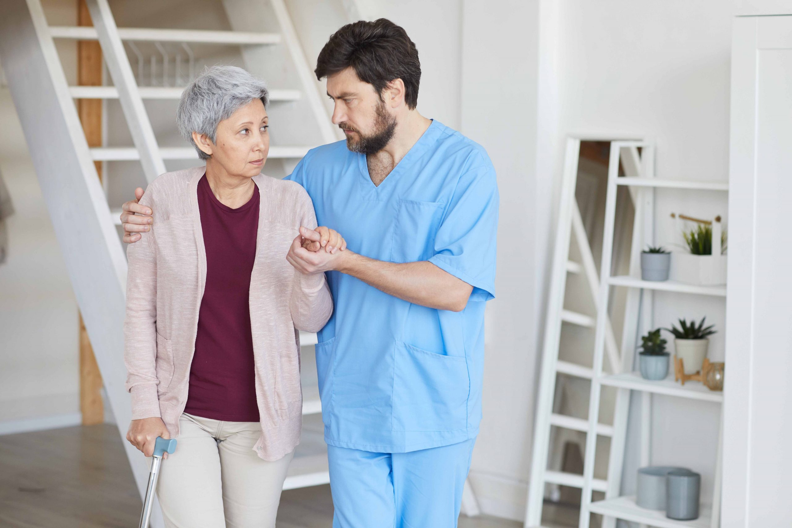 Mature bearded man in uniform caring for senior woman he helping her to move around the room
