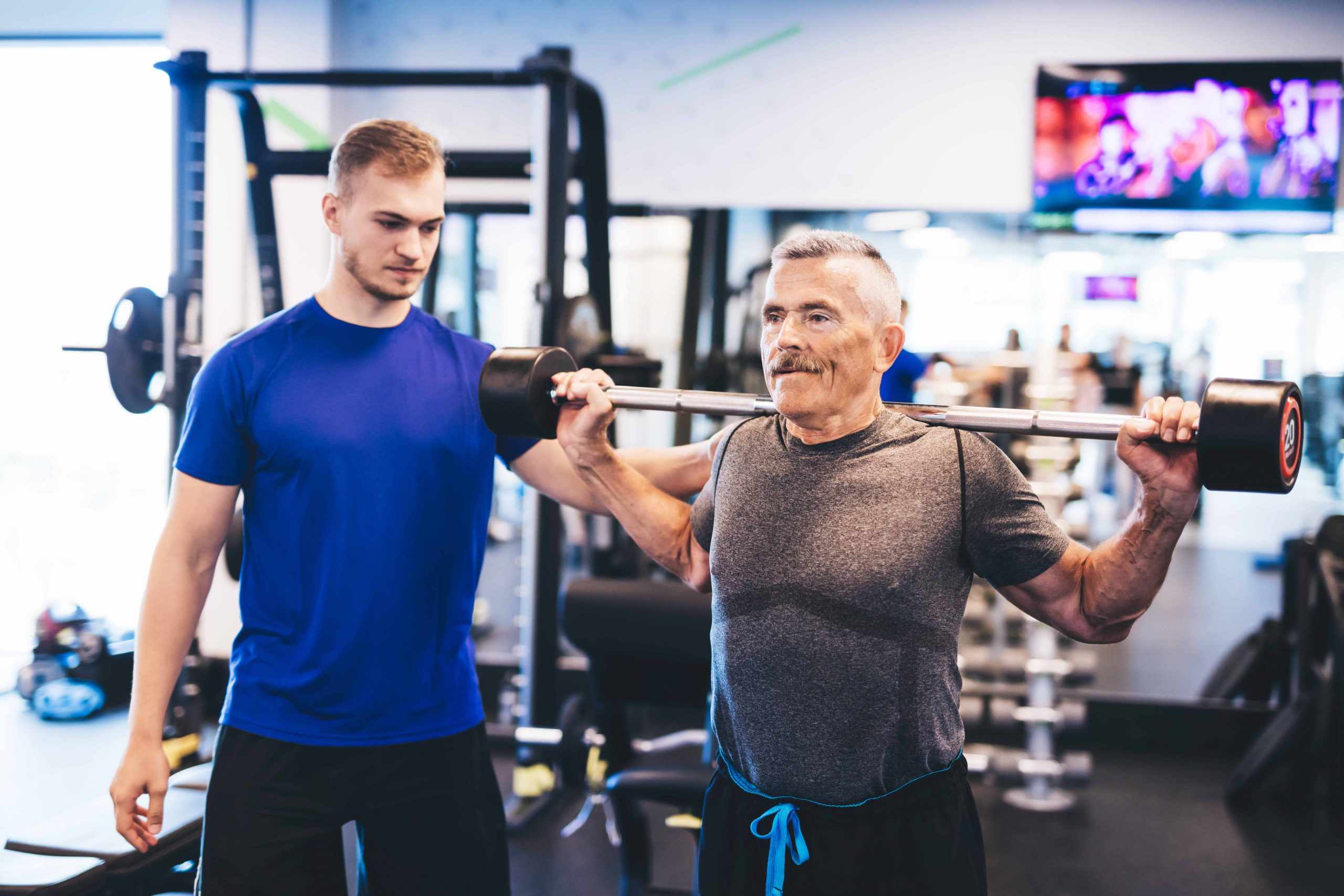 Older man and personal trainer at the gym. Lifting weights. Indoor workout.
