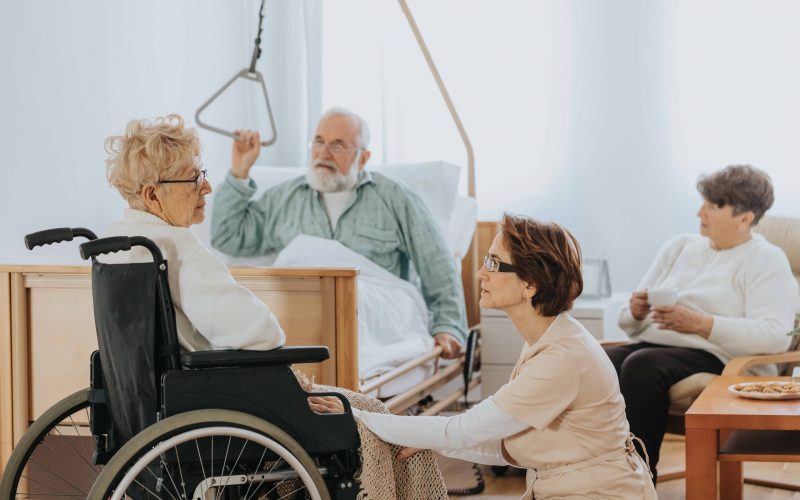 Sick elderly man sits on a hospital bed, a patient sits on his side in a wheelchair talking to a nurse kneeling in front of her