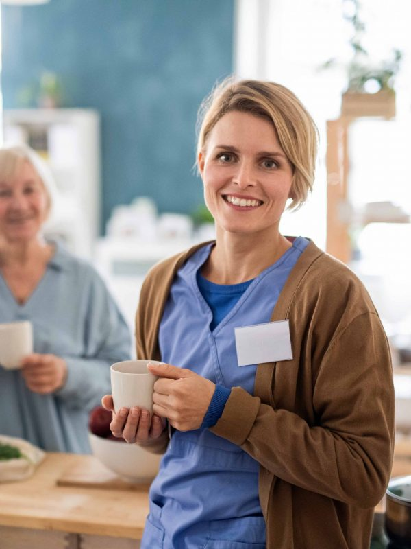 Portrait of senior woman with caregiver or healthcare worker indoors, drinking tea in kitchen.